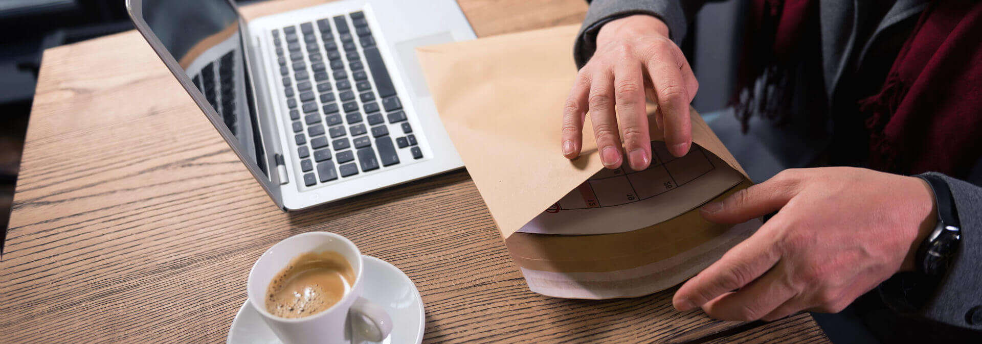 close up of a big paper envelope being filled with documents while being in hands of a handsome successful adult businessman