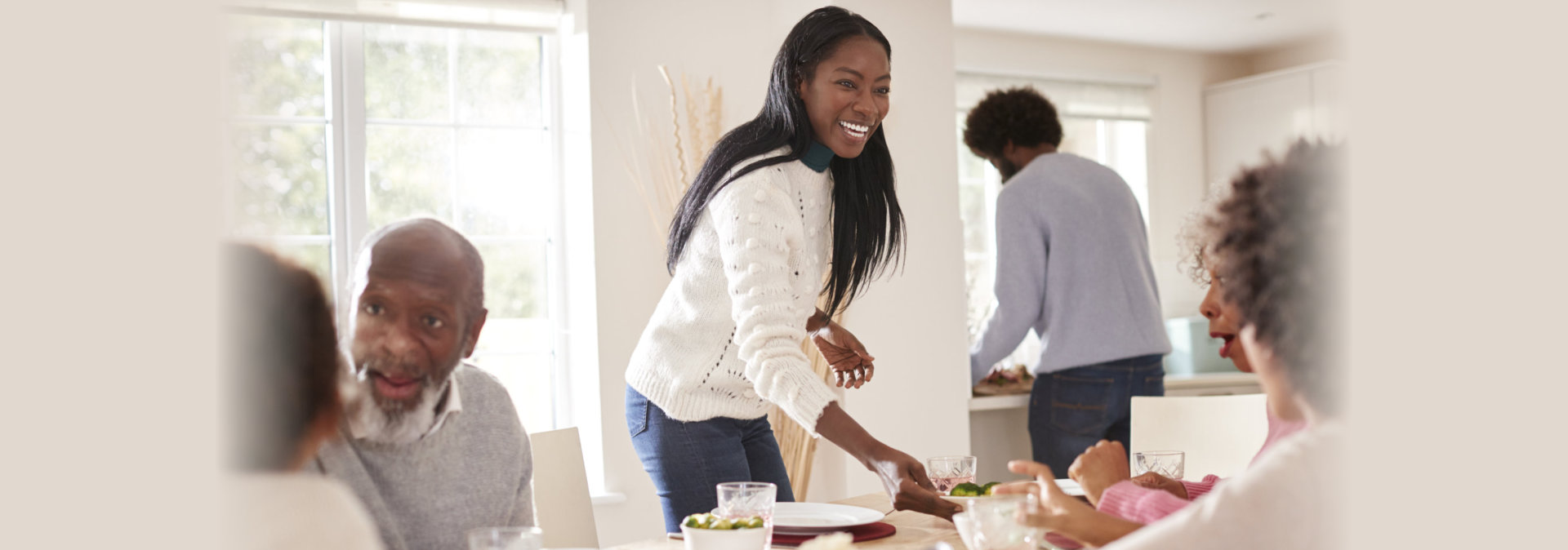Black couple bringing food to the table for Sunday family dinner